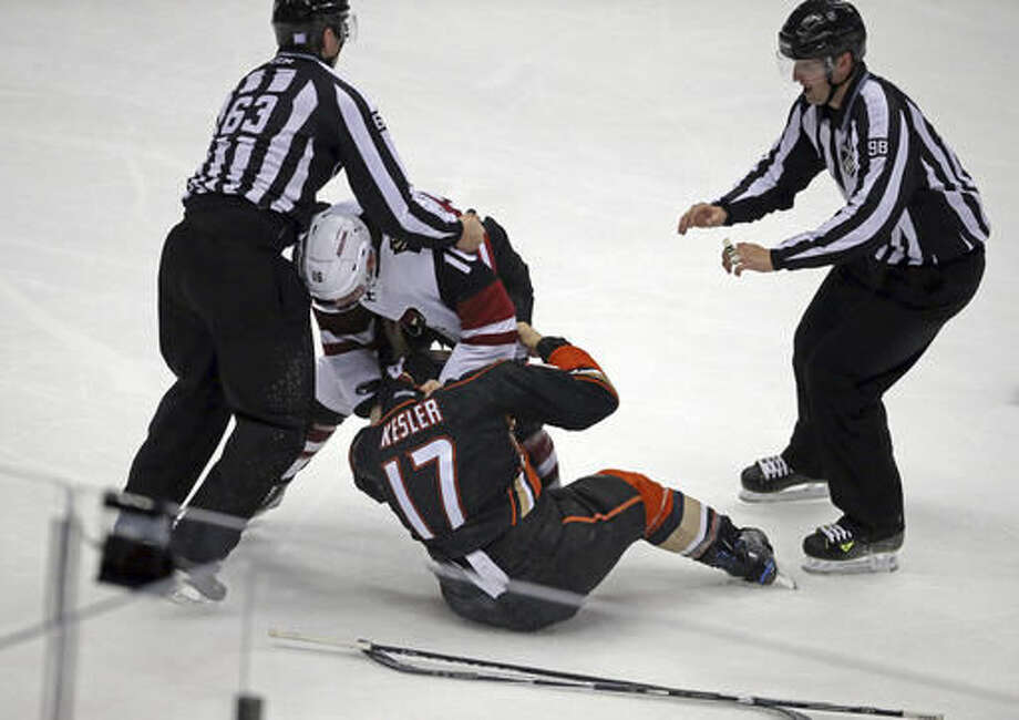 Arizona Coyotes left winger Max Domi (16) and Anaheim Ducks center Ryan Kesler (17) fight during the first period of an NHL hockey game in Anaheim, Calif., Friday, Nov. 4, 2016. (AP Photo/Reed Saxon)
