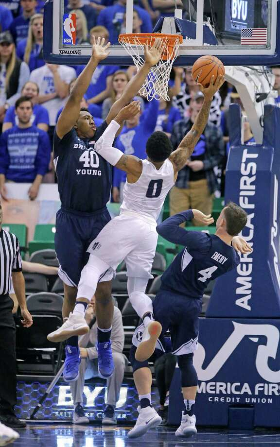 Utah State guard Shane Rector (0) goes to the basket as BYU's Jamal Aytes (40) and Nick Emery (4) defend in the first half during an NCAA college basketball game Wednesday, Nov. 30, 2016, in Salt Lake City. (AP Photo/Rick Bowmer) Photo: Rick Bowmer, STF / Copyright 2016 The Associated Press. All rights reserved.