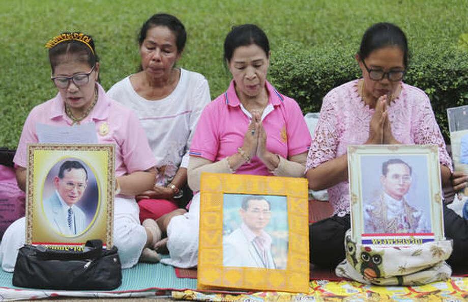 Thais pray behind portraits of Thailand's King Bhumibol Adulyadej at Siriraj Hospital where the king is being treated in Bangkok, Thailand, Wednesday, Oct. 12, 2016. (AP Photo/Sakchai Lalit)