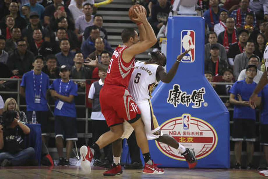 Ryan Anderson of the Houston Rockets in red tries to get past Lance Stephenson of the New Orleans Pelicans during a preseasons match in Beijing, China, Wednesday, Oct. 12, 2016. (AP Photo/Ng Han Guan)