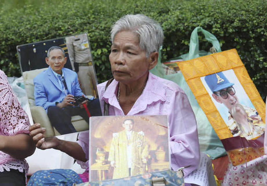 A Thai woman holds portraits of Thailand's King Bhumibol Adulyadej at Siriraj Hospital where the king is being treated in Bangkok, Thailand, Wednesday, Oct. 12, 2016. (AP Photo/Sakchai Lalit)