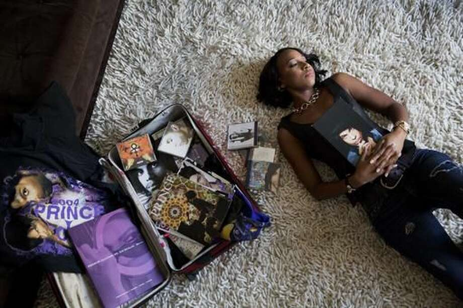 "Margo Davis poses for a portrait as she lays next to a collection of Prince memorabilia at her home in Smyrna, Ga., Tuesday, Oct. 11, 2016. Nearly 6 months after the legendary Prince was found dead in an elevator at his beloved Paisley Park, superfans are still in mourning. ""It's a spiritual connection for me,"" Davis said. ""I had to leave work when he passed. I didn't turn on the TV or pay attention to any of the tributes. I'm finally able to listen, but in a very limited way."" (AP Photo/David Goldman)"