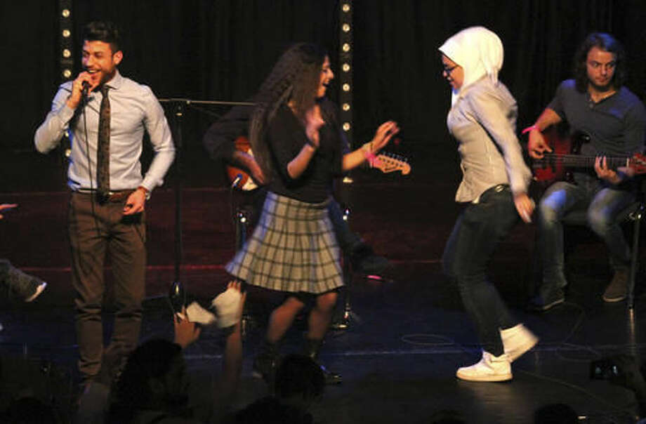 "In this Oct. 8, 2016 photo a group of women dance on stage during the performance by the Syrian band Musiqana at the ""Refugees in concert"" event in Berlin. Sounds from Syria took over a Berlin nightclub known for its punk, rock and techno music in a ""refugee concert"" organized to help break the ice between the new arrivals and residents of the German capital. (AP Photo/Jona Kallgren)"