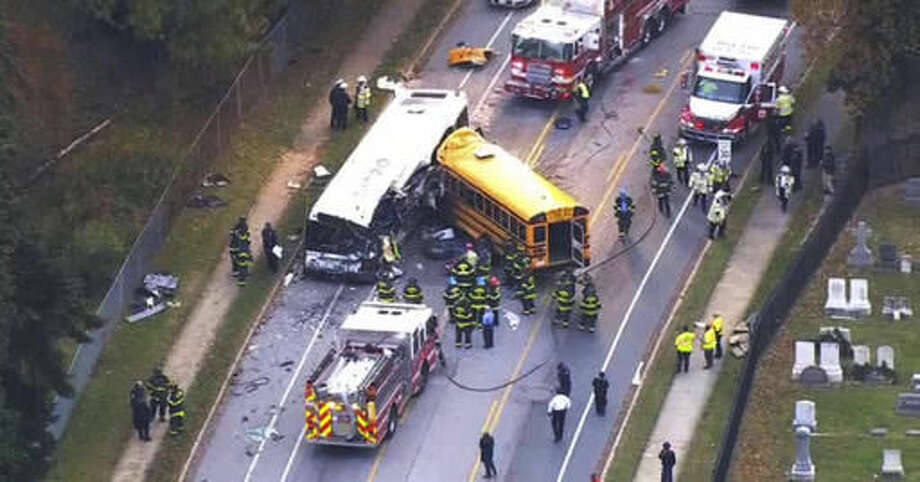 FILE - In this Tuesday, Nov. 1, 2016 frame from video, emergency personnel work at the scene of a fatal school bus and a commuter bus crash in Baltimore. The Maryland Motor Vehicle Administration says the driver of a Baltimore school bus involved in a deadly crash with a commuter bus shouldn't have been driving the vehicle because his commercial license had been suspended two months earlier. Glenn Chappell, 67, was killed Tuesday, along with a Maryland Transit Administration bus driver and four mass transit passengers, when his school bus crossed the center line and smashed into the commuter bus. No children were aboard. (WBAL-TV via AP, File)