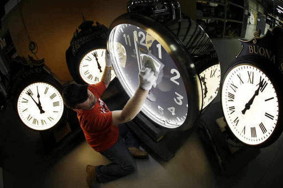 FILE-- In this Thursday, Nov. 3, 2016 photo, Dan LaMoore wipes down a Shinola clock at Electric Time Co., in Medfield, Mass. Daylight saving time ends at 2 a.m. local time Sunday, when clocks are set back one hour. A plan to eliminate Daylight Saving Time in California is moving forward. The measure to end the time change in California has come up before, but this is the furthest it's ever advanced.