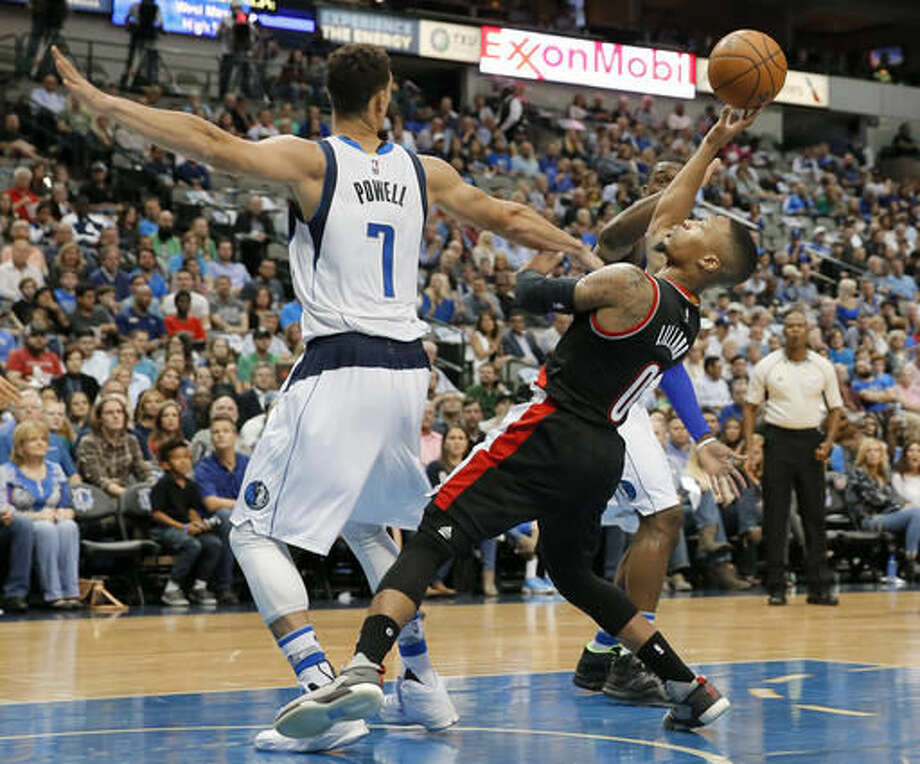 Dallas Mavericks forward Dwight Powell (7) defends as Portland Trail Blazers guard Damian Lillard (0) attempts a shot during the first half of an NBA basketball game, Friday, Nov. 4, 2016, in Dallas. (AP Photo/Tony Gutierrez)