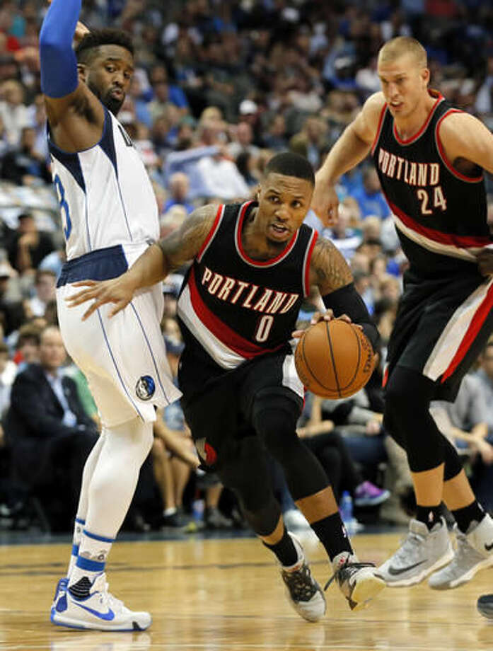 Portland Trail Blazers guard Damian Lillard (0) drives against Dallas Mavericks' Wesley Matthews (23) on his way to the basket as Mason Plumlee (24) follows during the first half of an NBA basketball game, Friday, Nov. 4, 2016, in Dallas. (AP Photo/Tony Gutierrez)