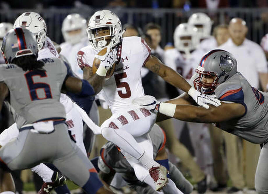 Temple running back Jahad Thomas (5) carries as Connecticut defensive lineman Mikal Myers, right, tries to bring him down during the first half of an NCAA college football game, Friday, Nov. 4, 2016, in East Hartford, Conn. (AP Photo/Elise Amendola)