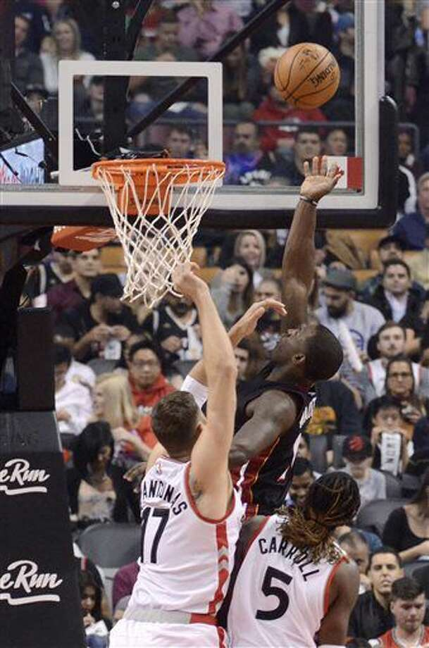 Miami Heat's Dion Waiters, center, shoots between Toronto Raptors' Jonas Valanciunas, left, and DeMarre Carroll during the first half of an NBA basketball game Friday, Nov. 4, 2016, in Toronto. (Jon Blacker/The Canadian Press via AP)