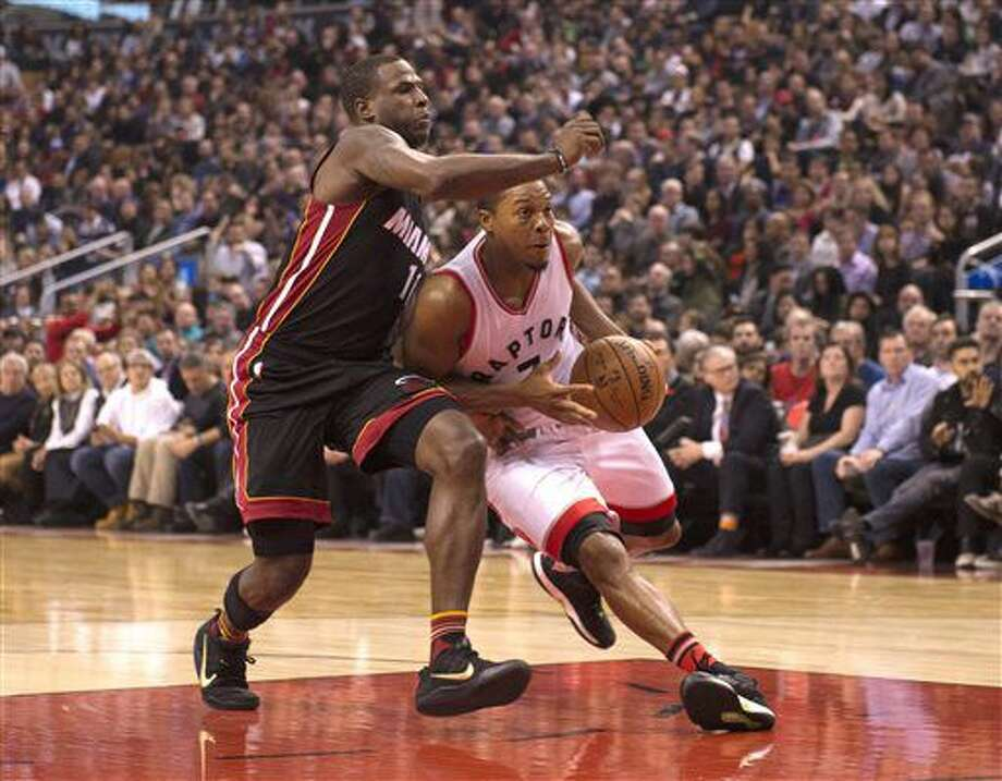 Toronto Raptors' Kyle Lowry ,right, gets around Miami Heat's Dion Waiters during the first half of an NBA basketball game Friday, Nov. 4, 2016, in Toronto. (Jon Blacker/The Canadian Press via AP)
