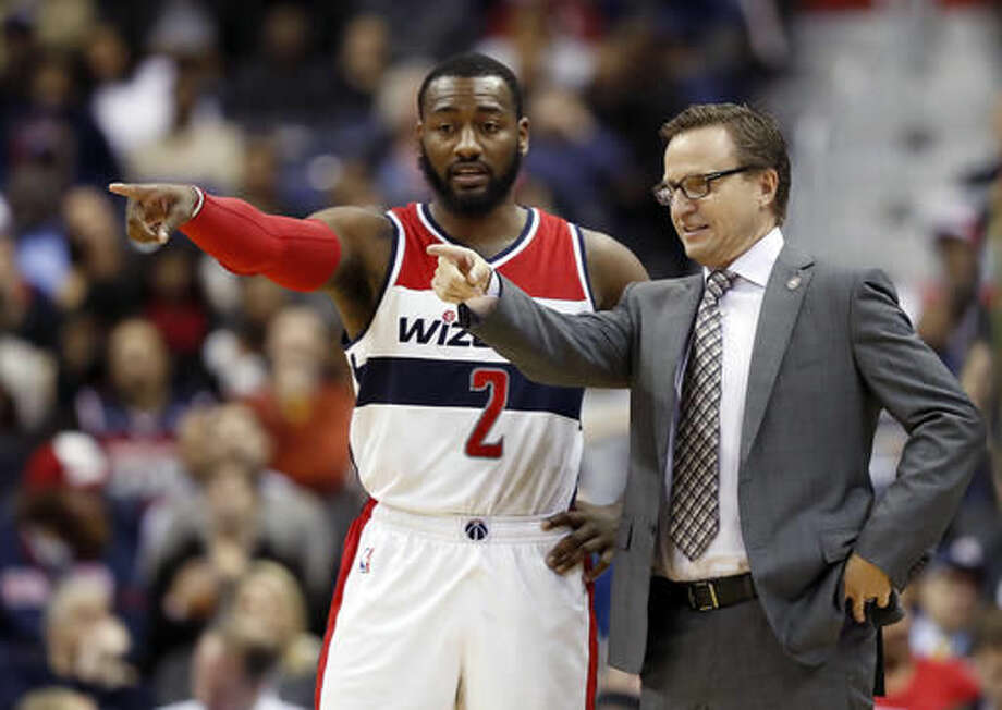 Washington Wizards guard John Wall and coach Scott Brooks talk during the first half of the team's NBA basketball game against the Atlanta Hawks, Friday, Nov. 4, 2016, in Washington. (AP Photo/Alex Brandon)