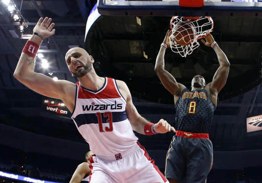 Washington Wizards center Marcin Gortat (13), from Poland, can't stop a dunk from Atlanta Hawks center Dwight Howard (8) during the first half of an NBA basketball game Friday, Nov. 4, 2016, in Washington. (AP Photo/Alex Brandon)