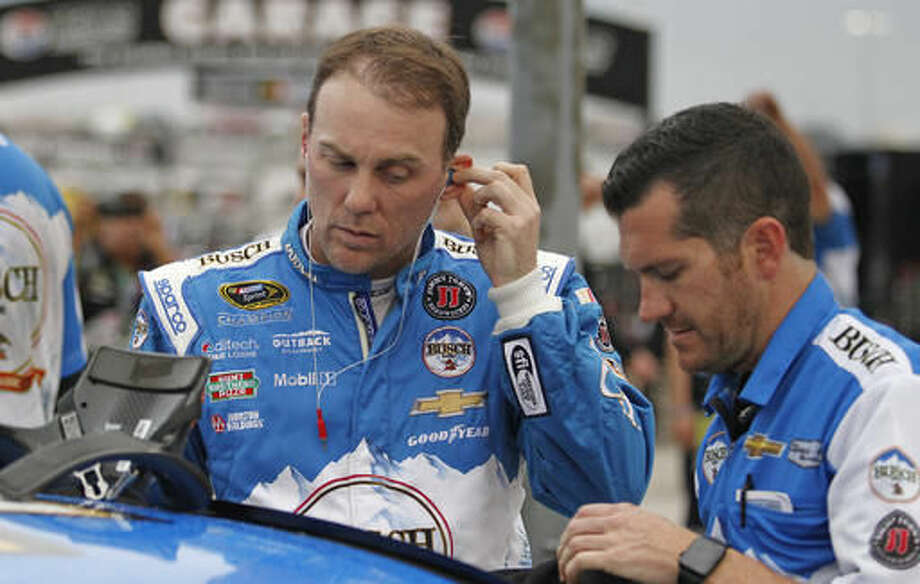 Kevin Harvick puts his radio earpieces in before qualifying for Sunday's NASCAR Sprint Cup auto race at Texas Motor Speedway, Friday, Nov. 4, 2016. (Paul Moseley/Star-Telegram via AP)