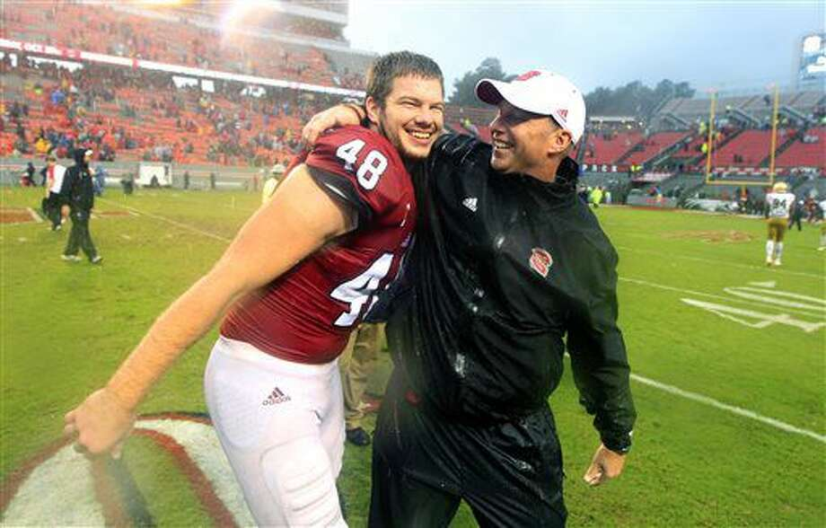 North Carolina State head coach Dave Doeren celebrates with Cole Cook (48) after their 10-3 victory over Notre Dame in an NCAA college football game at Carter-Finley Stadium in Raleigh, N.C., Saturday, Oct. 8, 2016. NC State won 10-3. (Ethan Hyman/The News & Observer via AP)
