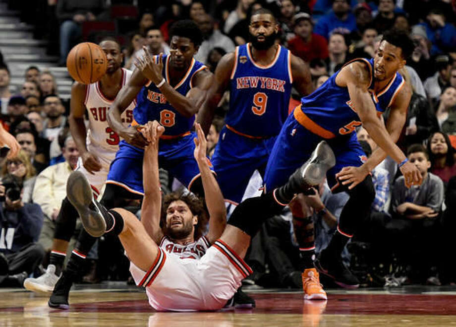 Chicago Bulls center Robin Lopez, bottom, passes the ball as New York Knicks guard Justin Holiday (8), forward Kyle O'Quinn (9) and guard Courtney Lee, right, watch during the first quarter of an NBA basketball game Friday, Nov. 4, 2016, in Chicago. (AP Photo/Matt Marton)