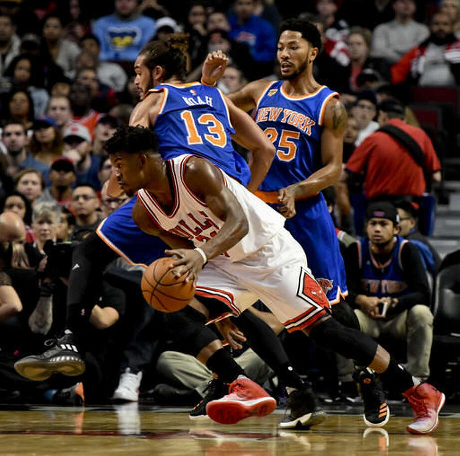 Chicago Bulls' Jimmy Butler, center, drives past New York Knicks center Joakim Noah (13) and New York Knicks guard Derrick Rose (25) during the first quarter of an NBA basketball game Friday, Nov. 4, 2016, in Chicago. (AP Photo/Matt Marton)