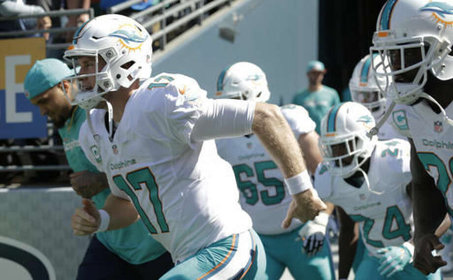 FILE - In this Sept. 11, 2016, file photo, Miami Dolphins quarterback Ryan Tannehill (17) runs out of the tunnel with his team before an NFL football game against the Seattle Seahawks, in Seattle. Tannehill has been sacked more than 200 times since he joined the Miami Dolphins, but he has never felt more pressure than this week, with the team off to a bad start and fans wanting a change at quarterback. (AP Photo/Stephen Brashear, File)