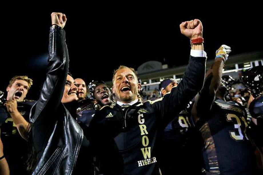 FILE - In this Saturday, Oct. 8, 2016, file photo, Western Michigan head coach P.J. Fleck celebrates with his team after their 45-3 win over Northern Illinois in an NCAA college football game in Kalamazoo, Mich. Western Michigan, off to its best start since 1941 at 6-0, is in the Top 25 for the first time with an offense averaging 45 points a game. The most impressive statistic, however, is that the Broncos are the only team in the nation that hasn't committed a turnover this season. (Chelsea Purgahn/Kalamazoo Gazette-MLive Media Group via AP, File)