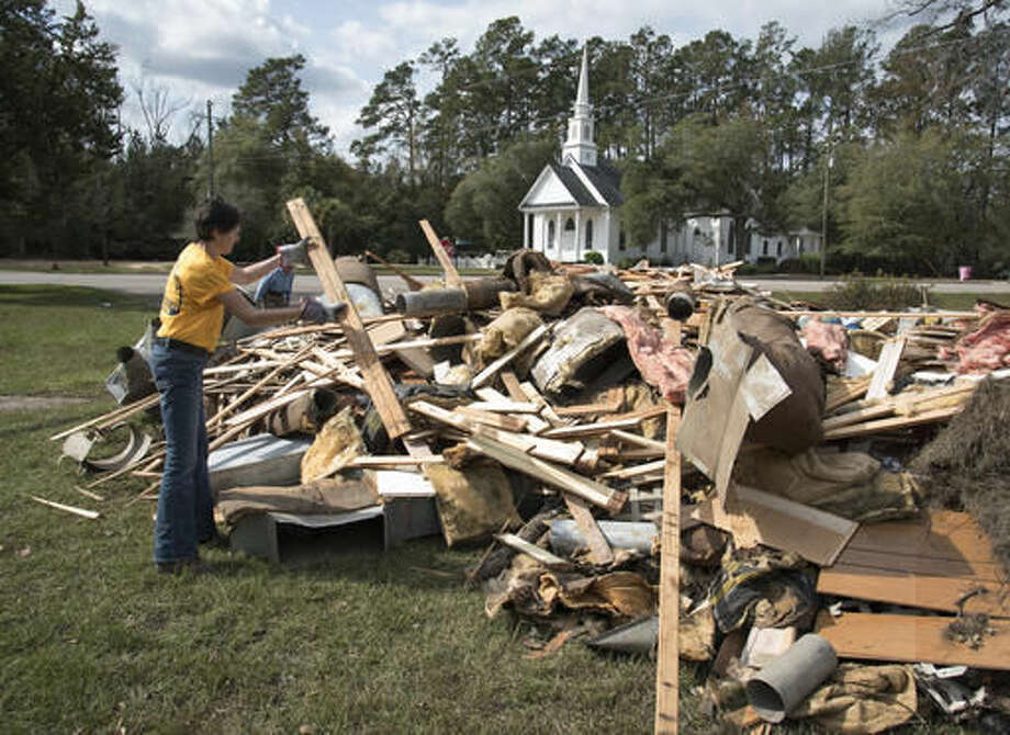 Wendy Gable, with Southern Baptist Convention Disaster Relief, throws wood onto a pile that was removed from a home that was heavily damaged by floodwaters caused by rain from Hurricane Matthew in Nichols, S.C., Thursday, Oct. 27, 2016. Nearly a month since floodwaters consumed the town, few have returned. The fear is that many never will. A stew of contaminants stood inches to feet deep in homes for a week. As it receded, toxic black mold grew rampant, leaving nearly all of the town's 261 homes uninhabitable. Few, if any, had flood insurance. (AP Photo/Mike Spencer)