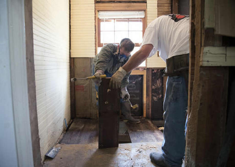 Ryan Ford, 34, removes water damaged flooring material from his home that was that was heavily damaged by floodwaters caused by rain from Hurricane Matthew in Nichols, S.C., Thursday, Oct. 27, 2016. Nearly a month since floodwaters consumed the town, few have returned. The fear is that many never will. A stew of contaminants stood inches to feet deep in homes for a week. As it receded, toxic black mold grew rampant, leaving nearly all of the town's 261 homes uninhabitable. Few, if any, had flood insurance. (AP Photo/Mike Spencer)
