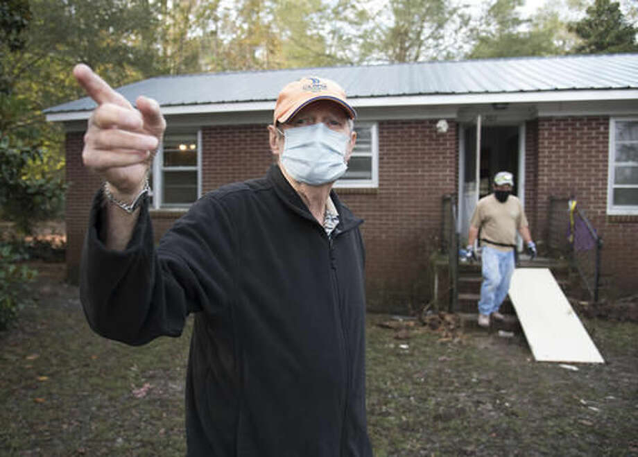 Bill Jones, 77, points towards a pile of debris removed from his home that was heavily damaged by floodwaters caused by rain from Hurricane Matthew in Nichols, S.C., Thursday, Oct. 27, 2016. Nearly a month since floodwaters consumed the town, few have returned. The fear is that many never will. A stew of contaminants stood inches to feet deep in homes for a week. As it receded, toxic black mold grew rampant, leaving nearly all of the town's 261 homes uninhabitable. Few, if any, had flood insurance. (AP Photo/Mike Spencer)