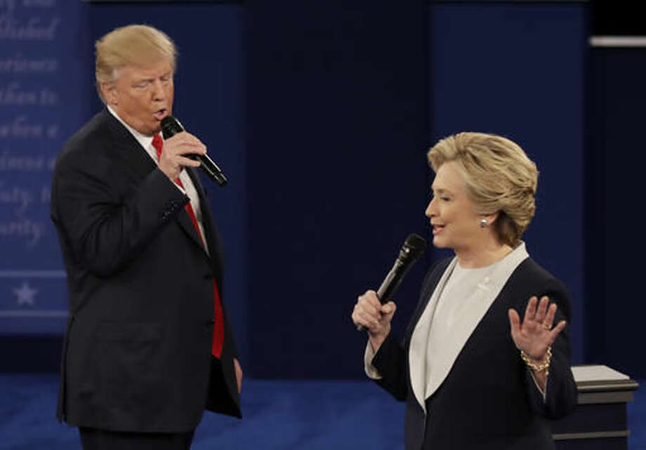 FILE - In this Sunday, Oct. 9, 2016, file photo, Republican presidential nominee Donald Trump and Democratic presidential nominee Hillary Clinton speak during the second presidential debate at Washington University in St. Louis. The contentiousness of the presidential election is spilling into some workplaces. And even when there's no rancor, more time is spent on election chatter than in the past. Rather than try to control what people are saying, owners should focus on whether the work is getting done in an atmosphere that's not hostile. (AP Photo/Patrick Semansky, File)