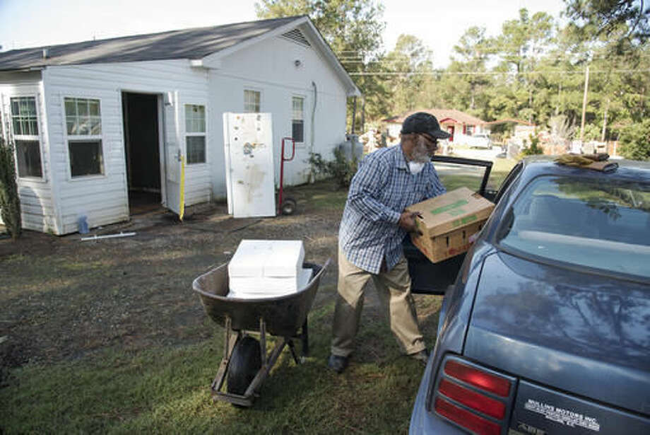 James Daniel Lee, 72, places boxes of personal items into his car after his home was heavily damaged by floodwaters caused by rain from Hurricane Matthew in Nichols, S.C., Thursday, Oct. 27, 2016. Nearly a month since floodwaters consumed the town, few have returned. The fear is that many never will. A stew of contaminants stood inches to feet deep in homes for a week. As it receded, toxic black mold grew rampant, leaving nearly all of the town's 261 homes uninhabitable. Few, if any, had flood insurance. (AP Photo/Mike Spencer)