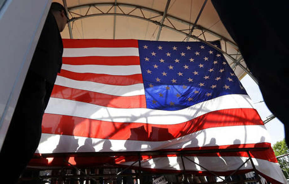 FILE - This Saturday, May 7, 2016 file photo shows the shadows of people standing behind Republican presidential candidate Donald Trump on a large U.S. flag, viewed from backstage in Lynden, Wash. In 2016, Americans are split over immigration, the changes wrought by globalization, the treatment of minorities and the threat of terrorism. But partisanship, long rising, has veered beyond policy disagreement. Now, roughly half of Democrats and Republicans tell pollsters they fear those in the other party. (AP Photo/Elaine Thompson)