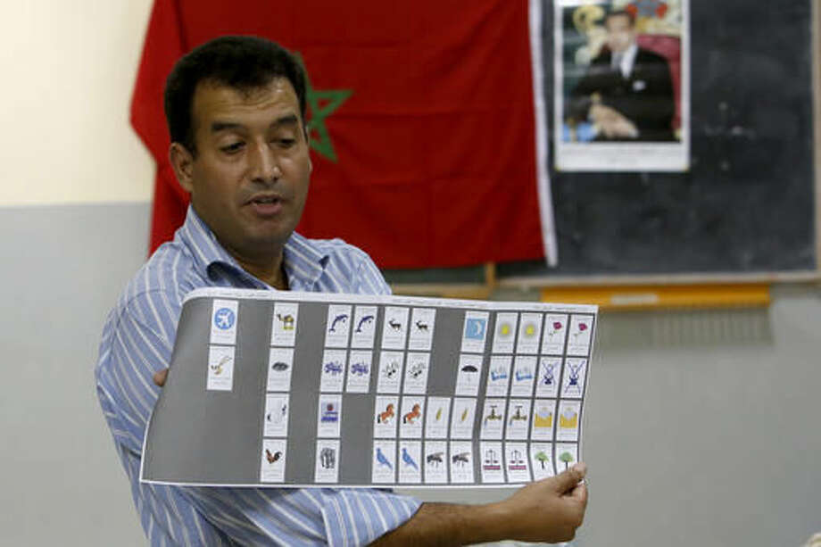 The president of a polling station shows a ballot as officials and political party's representatives count the ballots in the polling station in Rabat, Morocco, Friday, Oct. 7, 2016. Millions of Moroccans hit the voting booths, with worries about joblessness and extremism on many minds as they choose which party will lead their next government.(AP Photo/Abdeljalil Bounhar)