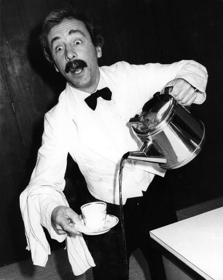 The world's worst waiter, Manuel from TV's 'Fawlty Towers', played by actor Andrew Sachs, demonstrates how much he needs to heed the advice contained in the new 'Tea Pack' training manual for caterers, 1981. Photo: Keystone/Getty Images