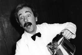 The world's worst waiter, Manuel from TV's 'Fawlty Towers', played by actor Andrew Sachs, demonstrates how much he needs to heed the advice contained in the new 'Tea Pack' training manual for caterers, 1981.