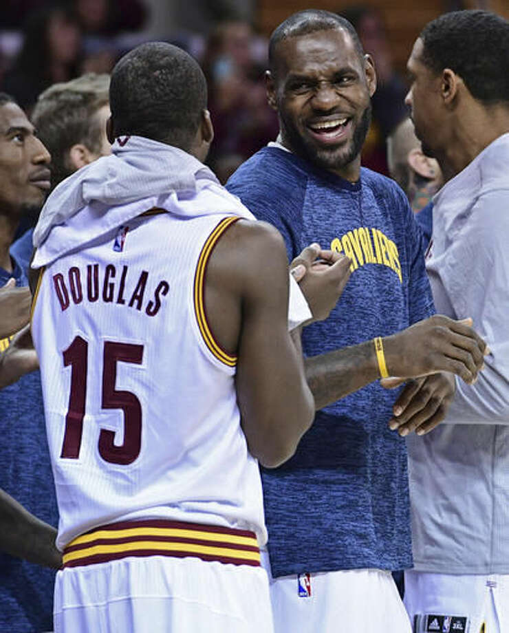 FILE- In this Oct. 8, 2016. file photo, Cleveland Cavaliers forward LeBron James (23) laughs with guard Toney Douglas (15) during the second half of an NBA preseason basketball game in Cleveland. NBA Commissioner Adam Silver and James are openly expressing their optimism for the NBA and its players being able to strike a new labor deal in the coming weeks. Either side can opt out of the current deal in December, and the sides are working to get something done before then. (AP Photo/David Dermer, File)