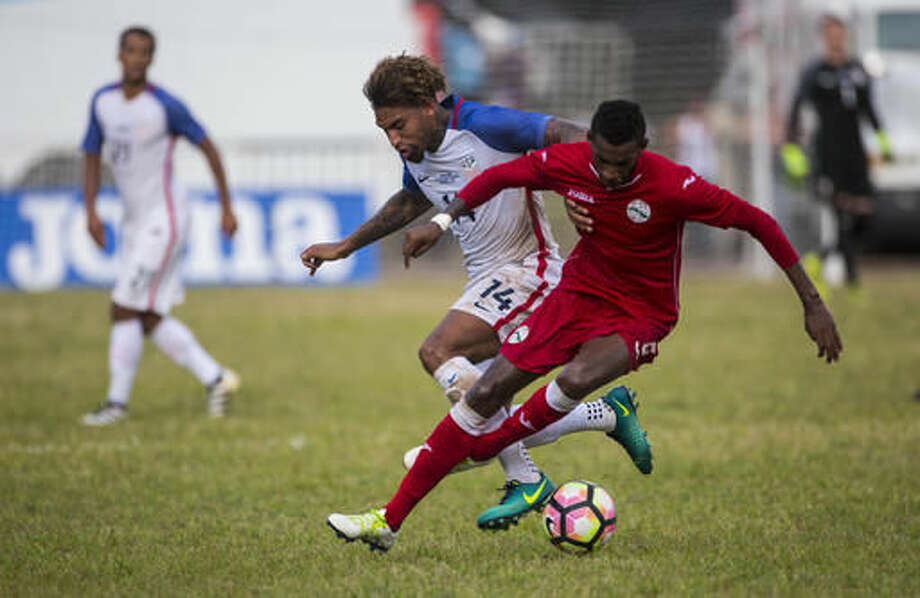 Danny Williams, of the U.S., left, and Cuba´s Duxney Alberto Espinosa, fight for control of the ball, during a friendly soccer match in the Pedro Marrero Stadium in Havana, Cuba, Friday, Oct. 7, 2016. The U.S. won the match 2-0. (AP Photo/Desmond Boylan)