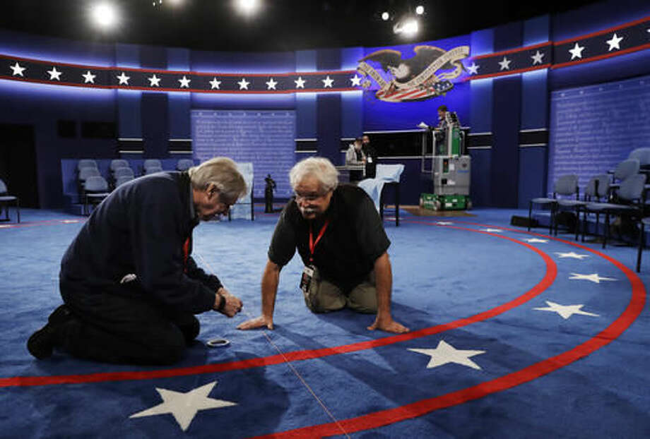 Workers prepare the stage for the second presidential debate between Republican presidential nominee Donald Trump Democratic presidential nominee Hillary Clinton at Washington University in St. Louis, Saturday, Oct. 8, 2016.(AP Photo/Patrick Semansky)