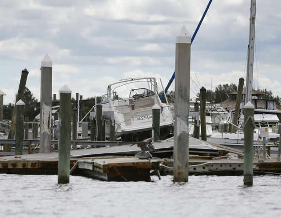 A boat rests on top of docks at a marina damaged by Hurricane Matthew in St. Augustine, Fla., on Saturday, Oct. 8, 2016. The fast-weakening storm continued its march along the Atlantic coast Saturday. (AP Photo/John Bazemore)