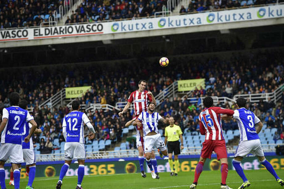 Atletico de Madrid' Diego Godin heads the ball beside Real Sociedad's Hector Hernandez during the Spanish La Liga soccer match between Real Madrid and Real Sociedad, at Anoeta stadium, in San Sebastian, northern Spain, Saturday, Nov.5, 2016. (AP Photo/Alvaro Barrientos)