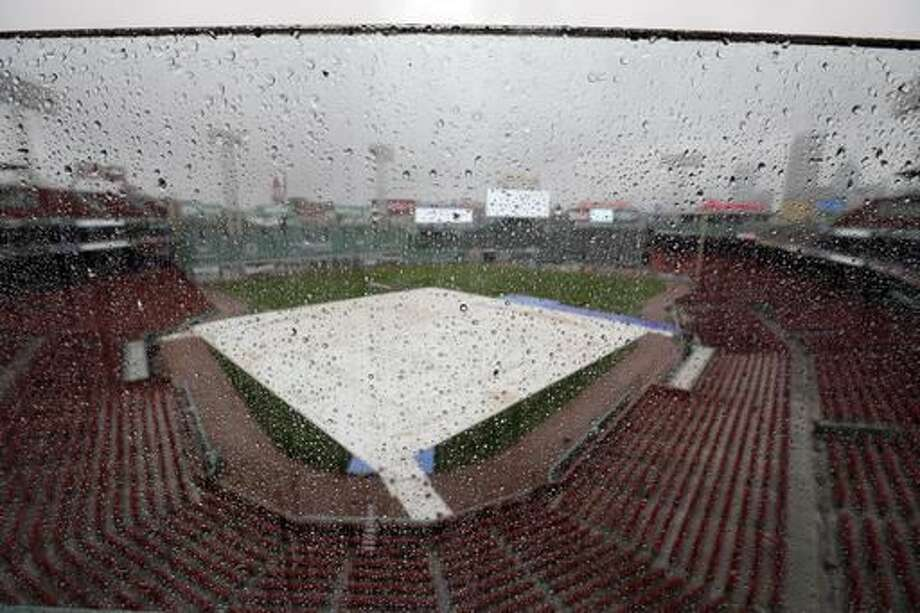 Rain drops cover a glass partition while a tarp covers the infield at Fenway Park during steady rain before Game 3 of baseball's American League Division Series between the Cleveland Indians and the Boston Red Sox, Sunday, Oct. 9, 2016, in Boston. (AP Photo/Elise Amendola)