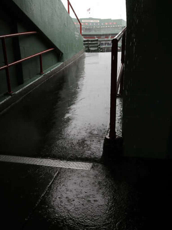 Rain drops splash in a puddle in an outfield concourse at Fenway Park during steady rain before Game 3 of baseball's American League Division Series between the Cleveland Indians and the Boston Red Sox, Sunday, Oct. 9, 2016, in Boston. (AP Photo/Charles Krupa)