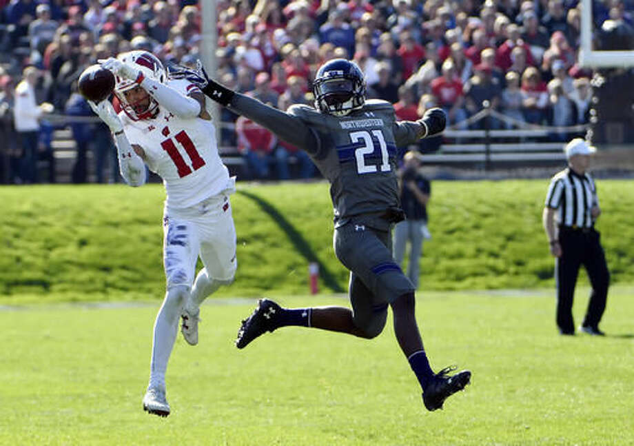 Wisconsin wide receiver Jazz Peavy (11) catches a pass in front of Northwestern safety Kyle Queiro (21) during the first half of an NCAA college football game in Evanston, Ill., Saturday, Nov. 5, 2016. (AP Photo/DavidBanks)