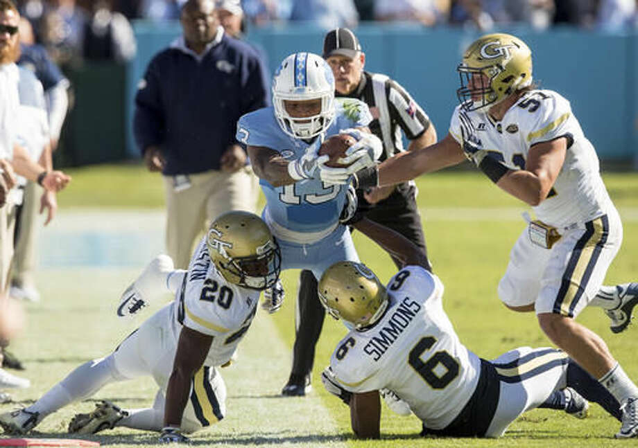 North Carolina's Bug Howard (13) attempts to stretch for a first down as Georgia Tech's Lawrence Austin (20), Lamont Simmons (6), and Brant Mitchell (51) defend during the first half of an NCAA college football game Chapel Hill, N.C., Saturday, Nov. 5, 2016. (AP Photo/Ben McKeown)