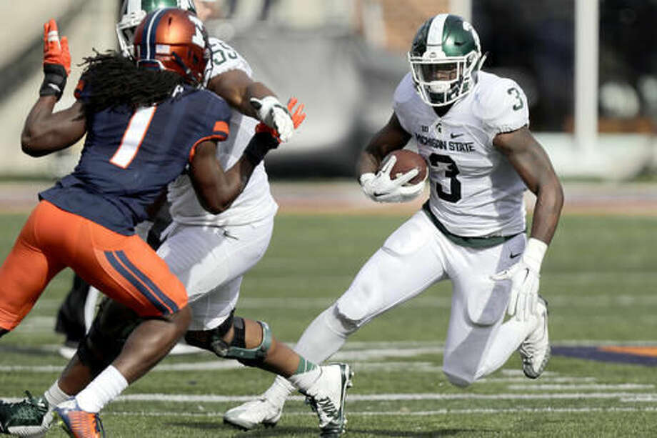 Michigan State running back LJ Scott (3) runs the ball against Illinois defensive back Jaylen Dunlap (1) during the first half of an NCAA college football game at Memorial Stadium Saturday, Nov. 5, 2016, in Champaign, Ill. (AP Photo/ Stephen Haas)