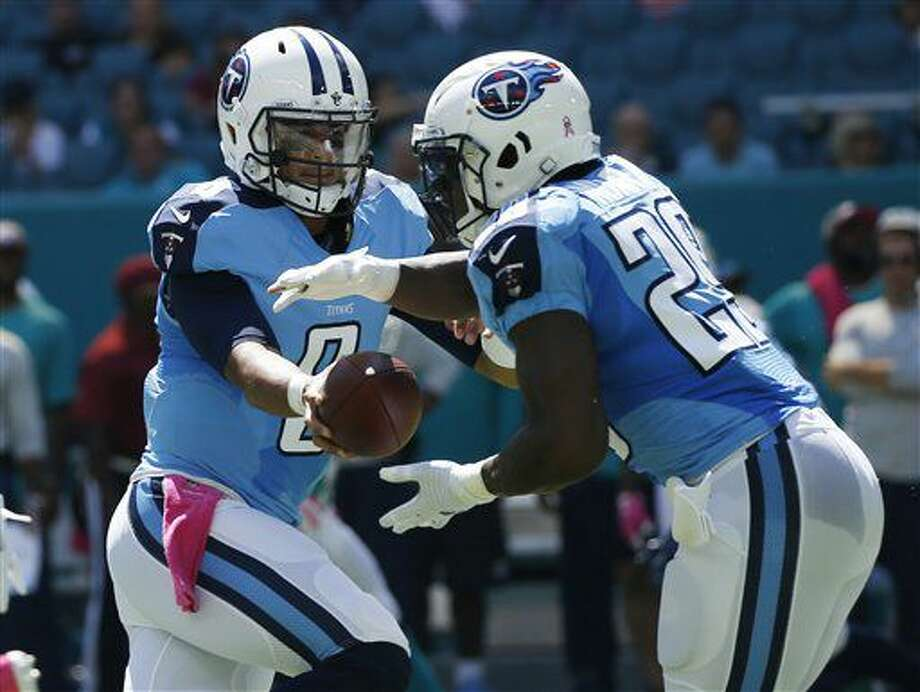 Tennessee Titans quarterback Marcus Mariota (8) hands the ball to running back DeMarco Murray (29) during the first half of an NFL football game, Sunday, Oct. 9, 2016, in Miami Gardens, Fla.(AP Photo/Joel Auerbach)