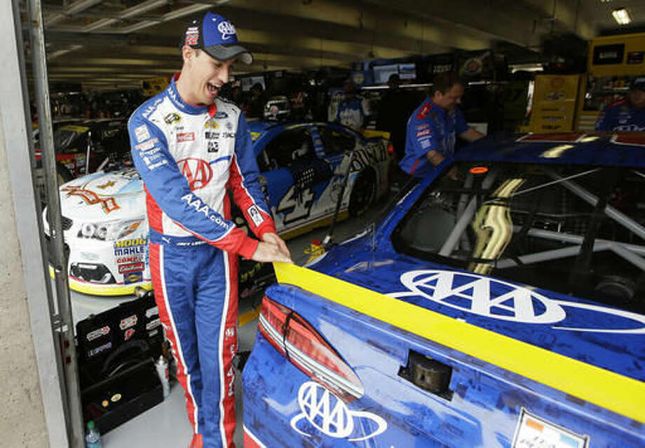Joey Logano laughs as he touches his car in the garage before the start of a NASACR Sprint Cup Series auto racing practice at Texas Motor Speedway in Fort Worth, Texas, Saturday, Nov. 5, 2016. (AP Photo/LM Otero)