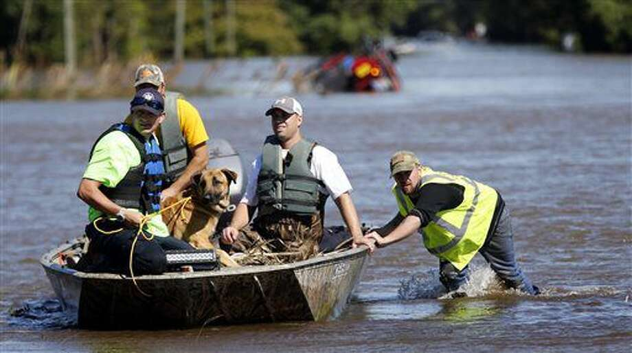South Edgecombe Fire and Rescue workers rescue several dogs that were trapped in homes flooded by rising water from Town Creek in Pinetops, N.C. on Sunday, Oct. 9, 2016. Hurricane Matthew's torrential rains triggered severe flooding in North Carolina on Sunday as the deteriorating storm made its exit to the sea, and thousands of people had to be rescued from their homes and cars. (Chris Seward/The Charlotte Observer via AP)