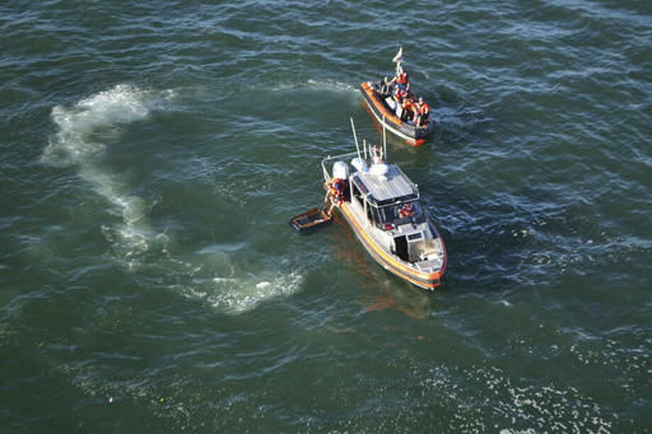 In this Oct. 8, 2016 photo, Coast Guard small boats clean up debris left behind by a boat, which capsized near Pier 45 just north of San Francisco, Calif. The boat capsized in the San Francisco Bay sending multiple adults and children to a hospital, officials said. (Petty Officer 2nd Class Chris Parrinello/U.S. Coast Guard via AP)