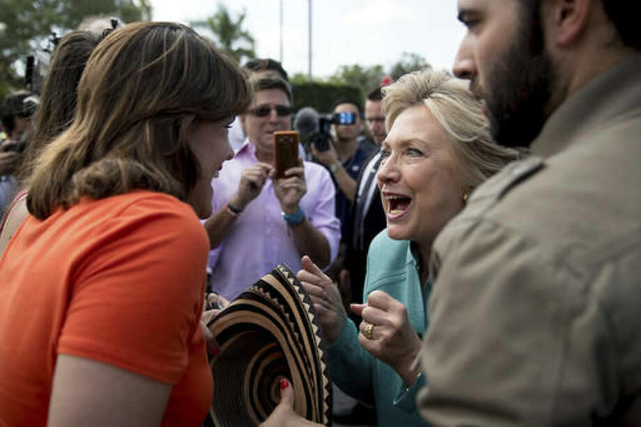 Democratic presidential candidate Hillary Clinton, center, accompanied by actor Jencarlos Canela, right, greets people outside an early voting center in West Miami, Fla., Saturday, Nov. 5, 2016. (AP Photo/Andrew Harnik)