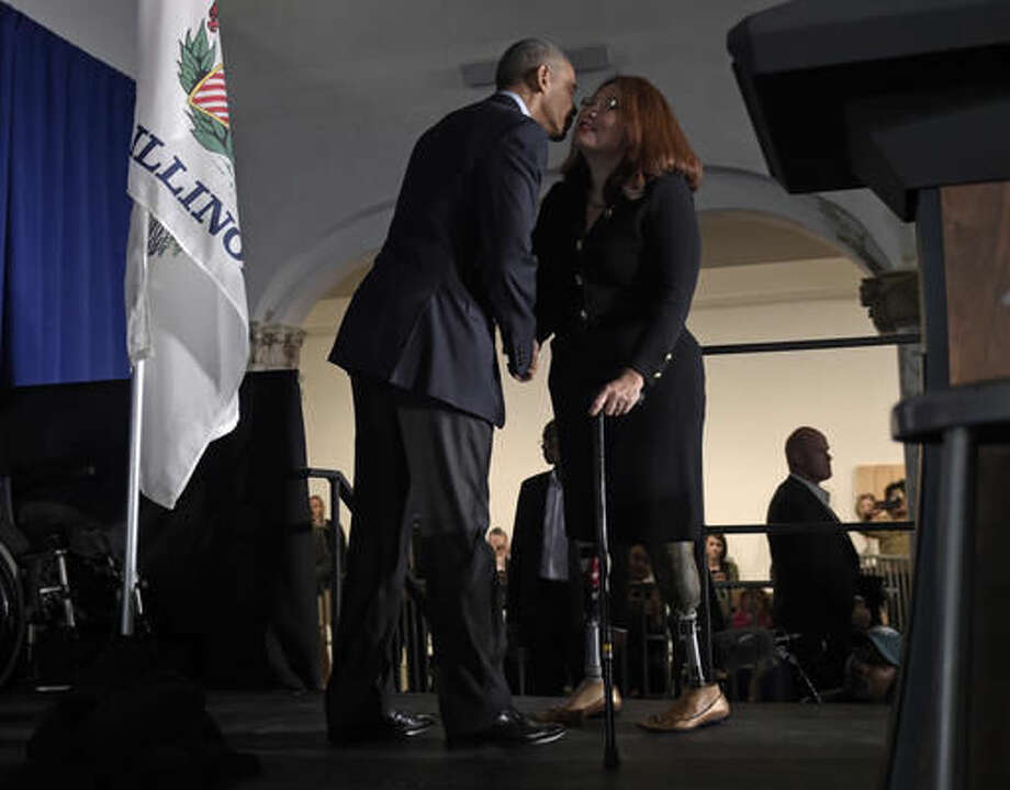 President Barack Obama, left, kisses Rep. Tammy Duckworth, D-Ill., right, before he speaks at the Stony Island Arts Bank during a fundraiser for Duckworth's Senate campaign in Chicago, Sunday, Oct. 9, 2016. Obama spent the weekend in Chicago where he voted, played golf and attended a fundraiser. (AP Photo/Susan Walsh)