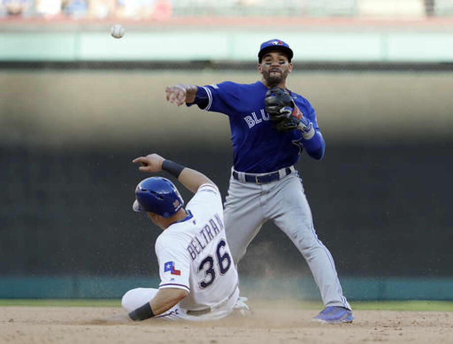 Toronto Blue Jays second baseman Devon Travis throws to first for the double play after forcing out Texas Rangers' Carlos Beltran during the seventh inning of Game 1 baseball's American League Division Series, Thursday, Oct. 6, 2016, in Arlington, Texas. Adrian Beltre was out at first. (AP Photo/David J. Phillip)