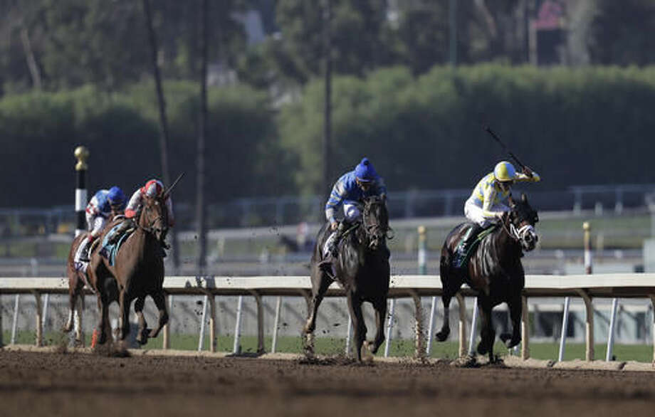 Classic Empire, right, with Julien Leparoux aboard charges to the finish line to win the Breeders' Cup Juvenile horse race at Santa Anita Park, Saturday, Nov. 5, 2016, in Arcadia, Calif. (AP Photo/Jae C. Hong)