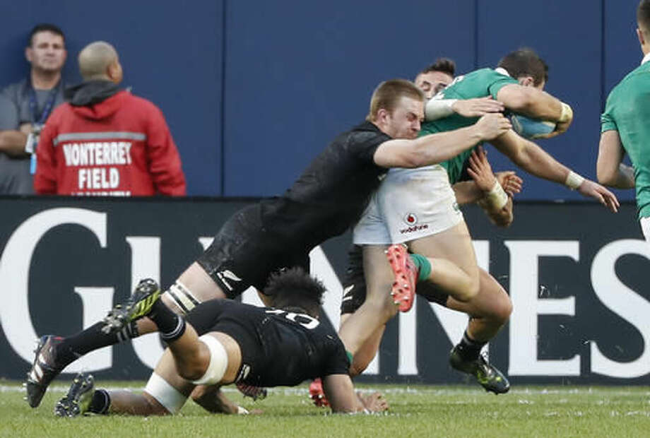 Ireland's Robbie Henshaw, right, scores past New Zealand's Sam Cane, left, during the second half of a rugby match Saturday, Nov. 5, 2016, in Chicago. (AP Photo/Kamil Krzaczynski)